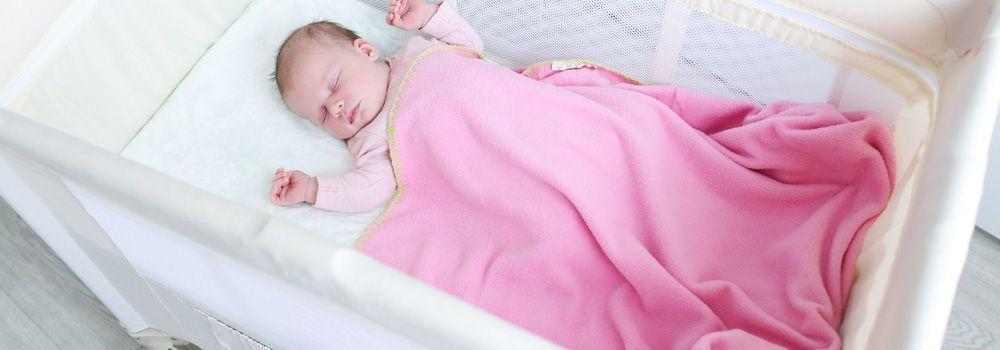 bébé dort, couverture rose et berceau blanc