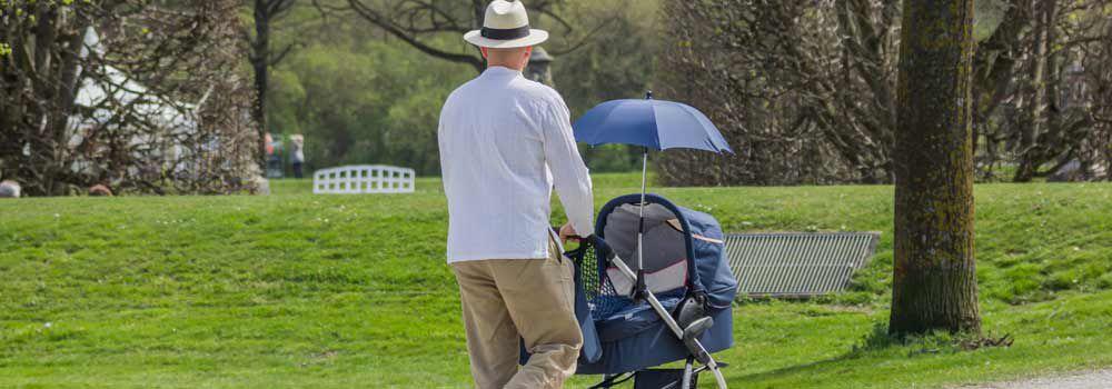 père avec son bébé dans une poussette