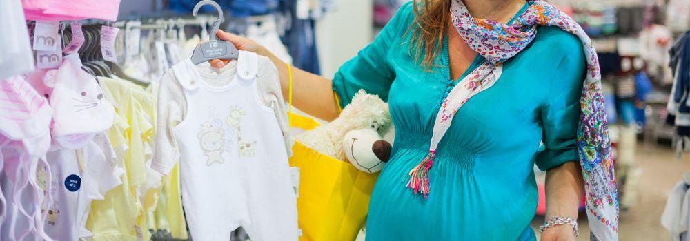 femme enceinte en train d'acheter des vêtements pour bébé