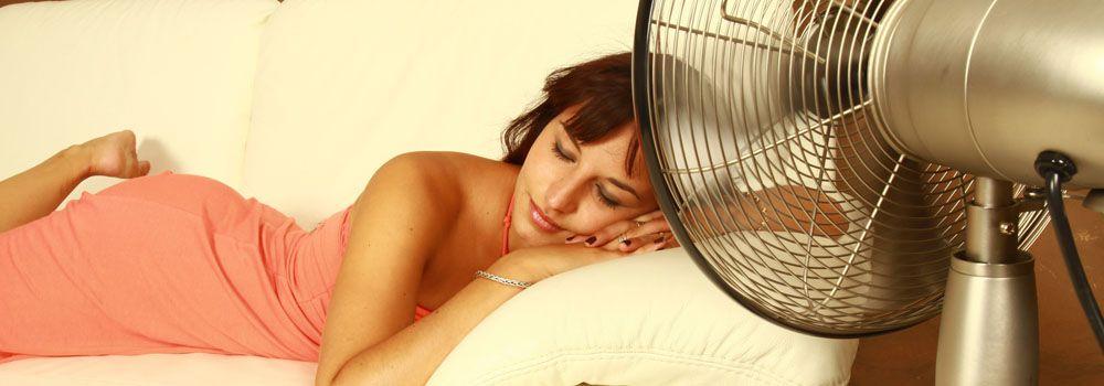 femme allongée dans son lit, ventilateur