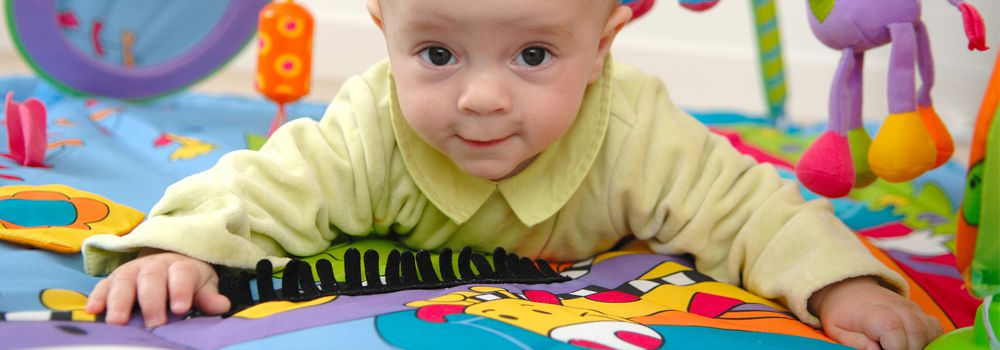 bébé s'amuse sur le tapis d'éveil