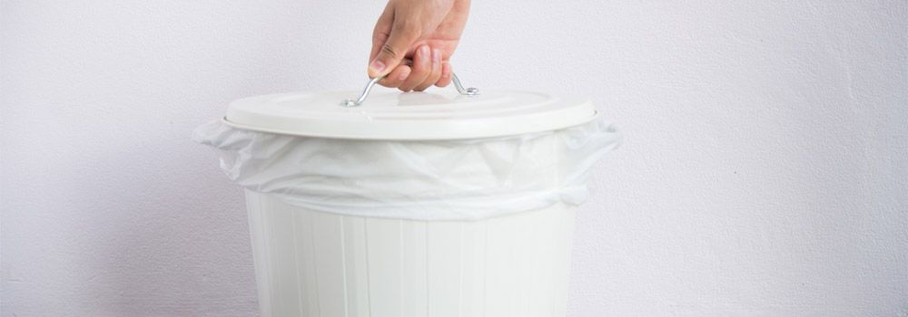mains en train de soulever le couvercle d'une poubelle blanche