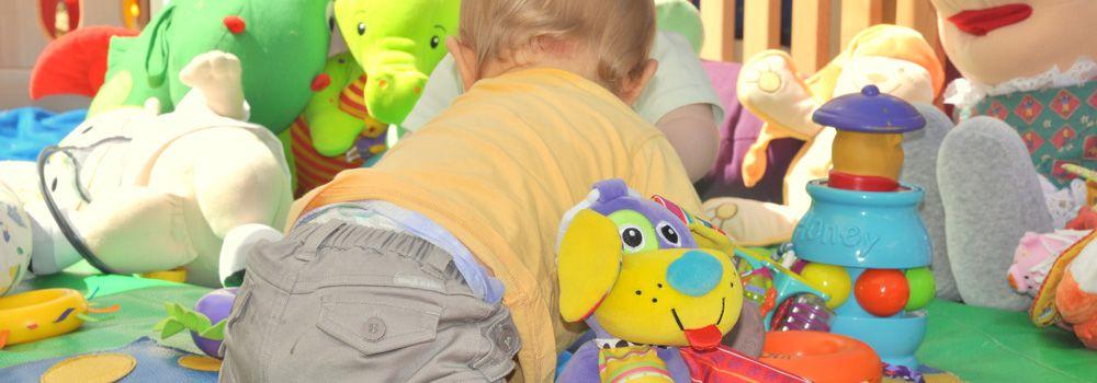 bébé avec ses jouets dans son parc
