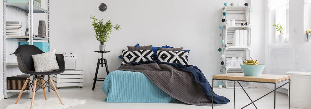 chambre : lit, table basse avec pied métallique et plateau en bois, fauteuil, étagère métallique