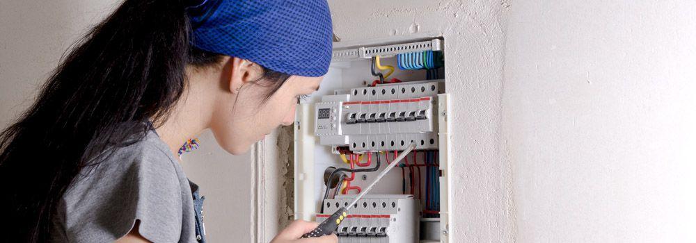 femme réparant l'installation électrique