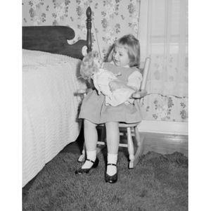 POUPÉE fille jouant avec une poupée à côté du lit en toil